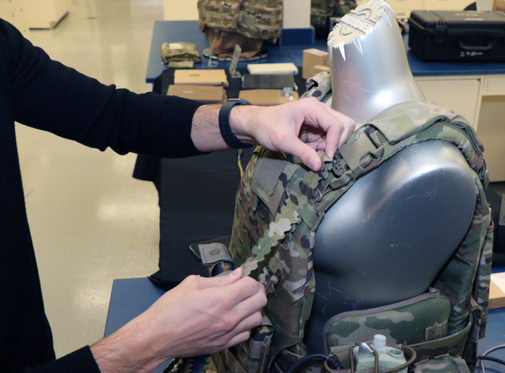 L'ingegnere Ethan Wise, ricercatore presso il C5ISR Center del Combat Capabilities Development Command (CCDC), collega i nuovi cavi di alimentazione integrati in un gilet tattico. (Dan Lafontaine, C5ISR Center Public Affairs)
