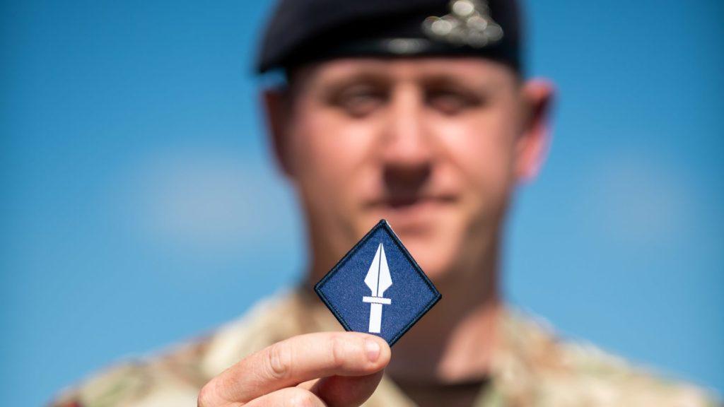 Un militare del 13th Signal Regiment mostra lo stemma dell'unità. (UK MoD)