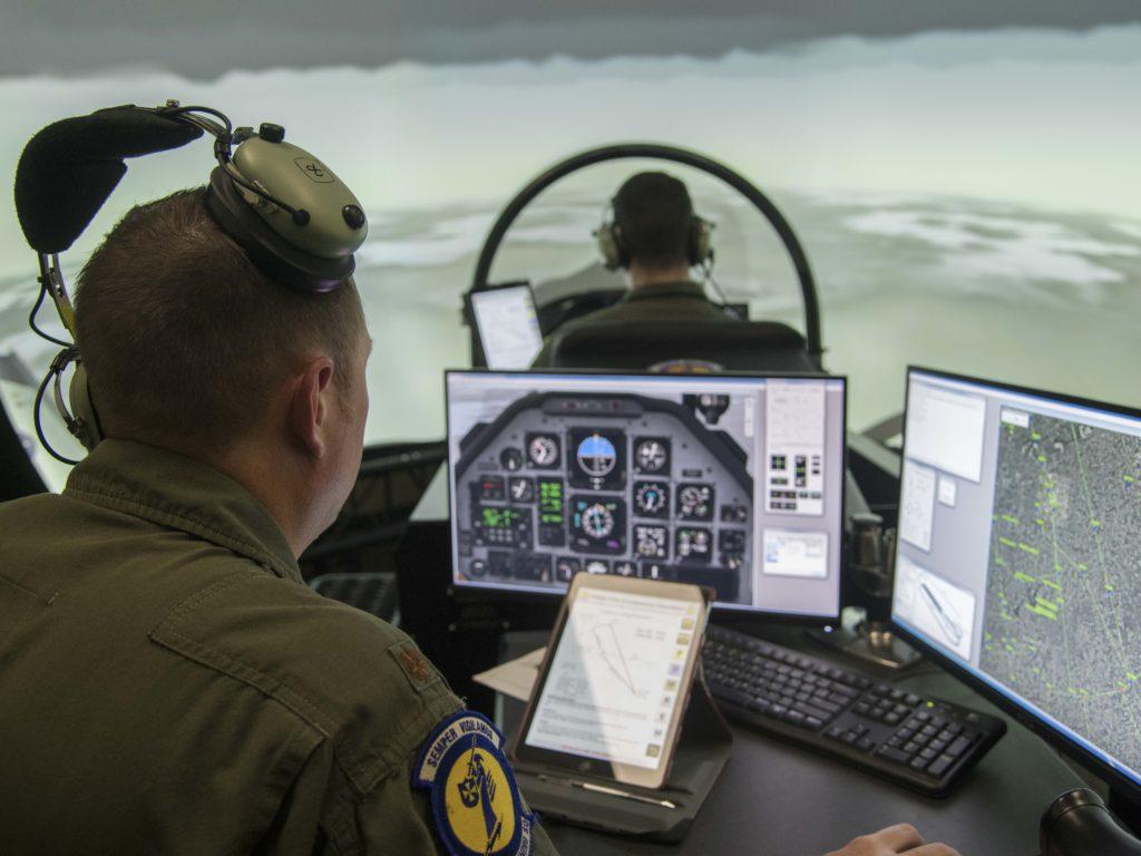 Un istruttore (in primo piano) supervisiona e istruisce un allievo RPA al simulatore del Texan T-6. (US Air Force)