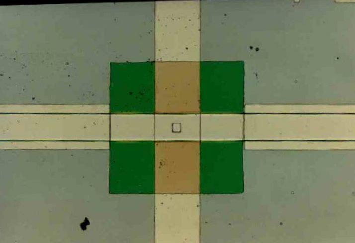 Una giunzione Josephson reale: la linea orizzontale è il primo elettrodo, mentre la linea verticale è il secondo elettrodo; il quadrato che li separa è un isolante che ha al centro, dove si incrociano i due elettrodi, una piccola apertura attraverso cui si ha la vera e propria giunzione Josephson. (Fonte: Wikipedia)