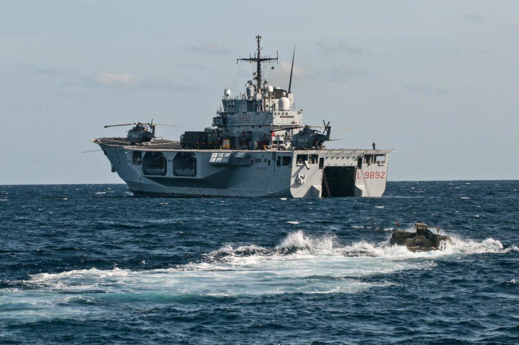 """La nave anfibia (LPD) San Giorgio è l'attuale nave ammiraglia (flagship) dell'Operazione Irini. Consegnata alla Marina Militare il 9 ottobre 1987, dal 2000 al 2002 è stata oggetto di lavori che l'hanno portata all'attuale configurazione """"tutto ponte"""", con 4 differenti spot per operazioni di volo con elicotteri. (Fonte: Marina Militare)"""